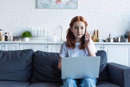 Photo pour Rousse fille regardant caméra tout en parlant sur téléphone mobile près d'un ordinateur portable - image libre de droit