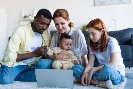Photo pour Interracial famille assis sur le sol et regarder film sur ordinateur portable - image libre de droit