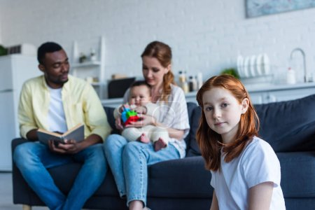 Photo pour Rousse preteen fille regardant caméra près de multiethnique famille assis sur canapé sur fond flou - image libre de droit