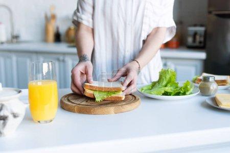 abgeschnittene Ansicht einer Frau mit Sandwich beim Zubereiten des Frühstücks