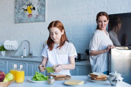 ruda dziewczyna przygotowanie kanapki na śniadanie w pobliżu szczęśliwy mama