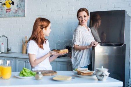 preteen girl showing sandwich to happy mom in kitchen