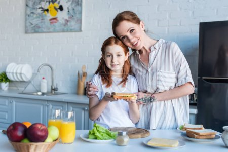 smiling girl holding sandwich near happy mother embracing her in kitchen
