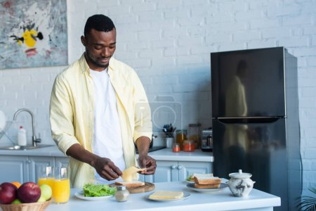 african american man making sandwich with cheese and lettuce in kitchen