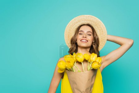 Photo for Cheerful woman in sun hat holding tulips isolated on blue - Royalty Free Image