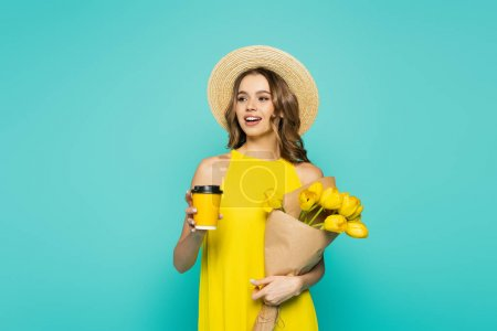 Smiling woman in sun hat holding coffee to go and tulips isolated on blue