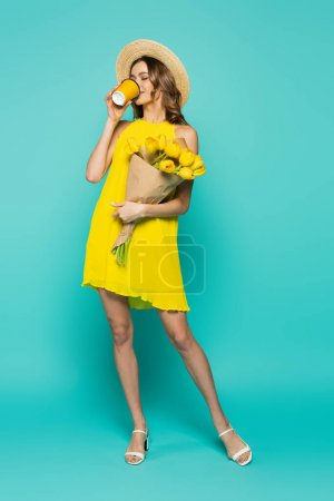 Woman in straw hat and yellow dress drinking coffee and holding tulips on blue background