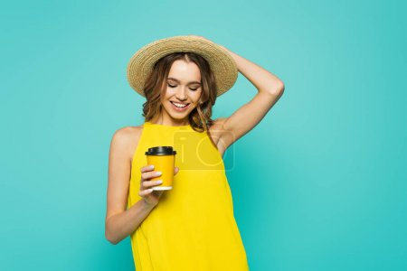 Happy woman in sun hat holding coffee to go isolated on blue