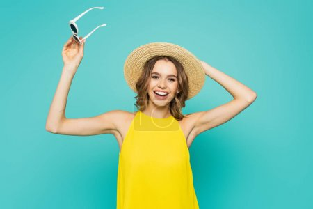 Cheerful woman holding sunglasses and straw hat isolated on blue