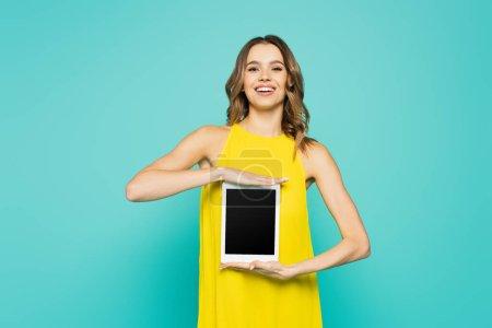 Femme souriante montrant tablette numérique avec écran blanc isolé sur bleu
