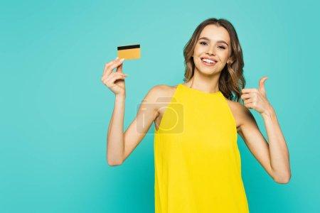 Photo pour Femme souriante avec carte de crédit montrant comme isolé sur bleu - image libre de droit