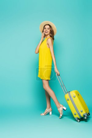 Stylish woman in dress and sun hat holding suitcase on blue background