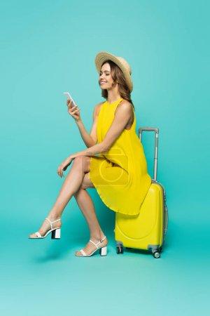 Photo pour Femme souriante en robe en utilisant smartphone sur valise sur fond bleu - image libre de droit