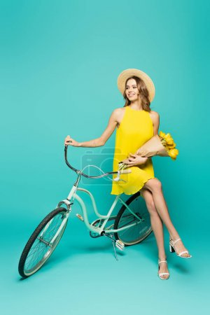 Smiling woman in sun hat holding tulips near bicycle on blue background