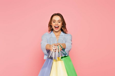 Photo for Excited shopaholic holding shopping bags isolated on pink - Royalty Free Image