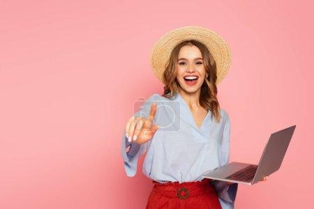Photo pour Femme gaie en chapeau de paille pointant du doigt tout en tenant l'ordinateur portable isolé sur rose - image libre de droit