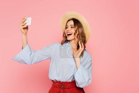 Photo pour Femme gaie en chapeau de paille ayant appel vidéo sur smartphone isolé sur rose - image libre de droit