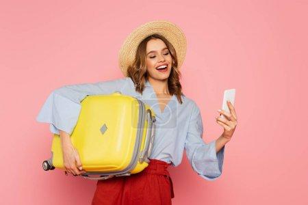 Photo pour Femme souriante avec valise utilisant un smartphone isolé sur rose - image libre de droit