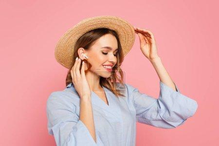 Photo pour Femme élégante en chapeau de soleil et écouteur isolé sur rose - image libre de droit