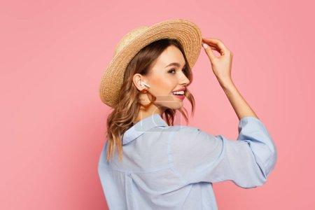 Photo pour Vue latérale du modèle heureux en chapeau de paille et écouteur isolé sur rose - image libre de droit