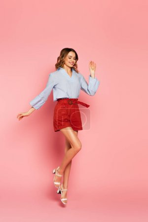 Stylish woman jumping on pink background