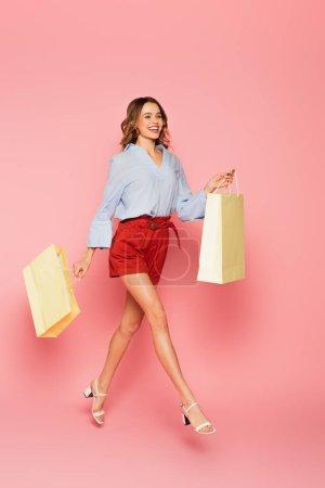 Photo pour Femme souriante avec des sacs à provisions sautant sur fond rose - image libre de droit