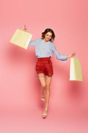 Photo pour Femme positive sautant et tenant des sacs à provisions sur fond rose - image libre de droit