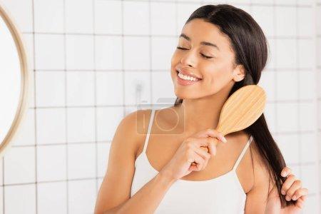 Photo pour Sourire jeune femme afro-américaine brossant les cheveux avec les yeux fermés près du miroir dans la salle de bain - image libre de droit