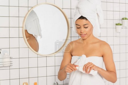 young african american woman wrapped in towels holding toothbrush and toothpaste in bathroom