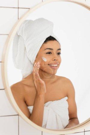 joven afroamericana mujer envuelta en toallas aplicando crema en la cara y mirando en el espejo en el baño
