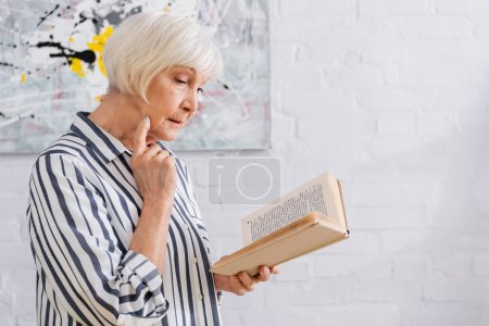 Photo for Senior woman in striped shirt reading book at home - Royalty Free Image