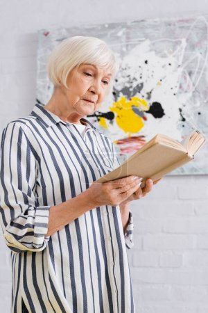 Photo for Senior woman in casual clothes reading book at home - Royalty Free Image