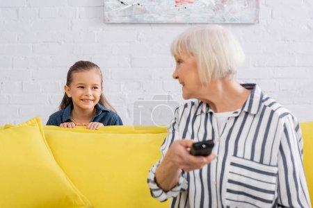 Photo pour Enfant souriant à la grand-mère avec télécommande au premier plan flou - image libre de droit