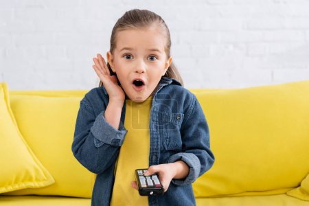 Photo for Astonished kid with remote controller sitting on couch - Royalty Free Image
