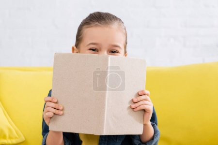 Photo for Child covering face with book on blurred couch - Royalty Free Image