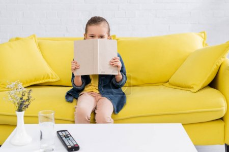 Photo for Girl holding book near face on couch at home - Royalty Free Image