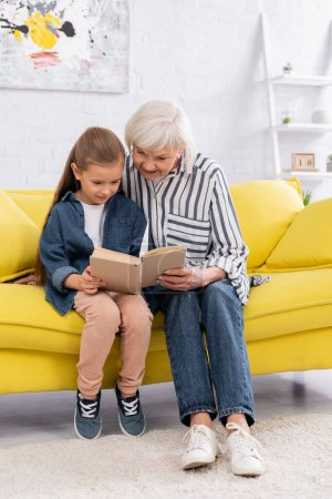 Photo for Smiling granny and child reading book together on couch - Royalty Free Image