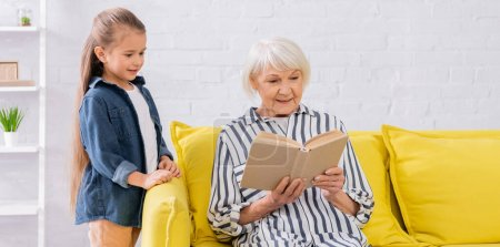 Photo for Smiling elderly woman reading book near kid in living room, banner - Royalty Free Image