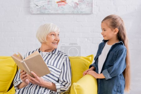 Photo for Granny with book looking at positive granddaughter in living room - Royalty Free Image