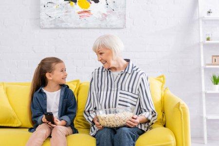 Photo pour Enfant souriant avec télécommande regardant mamie avec pop-corn - image libre de droit