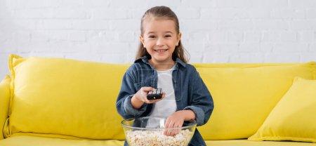Photo pour Enfant joyeux tenant télécommande et pop-corn dans le salon, bannière - image libre de droit
