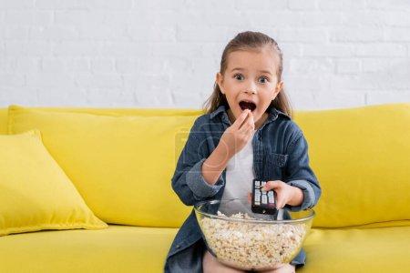 Photo pour Fille excitée avec télécommande manger pop-corn - image libre de droit