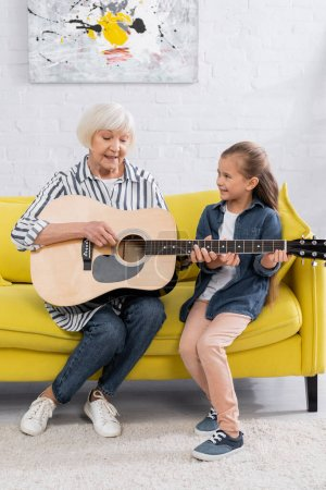 Photo pour Joyeux grand-mère et enfant jouant de la guitare acoustique sur le canapé - image libre de droit