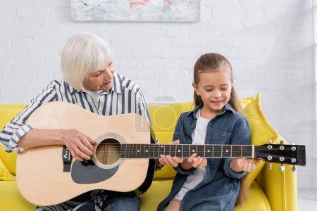 Photo pour Enfant heureux jouant de la guitare acoustique avec mamie dans le salon - image libre de droit