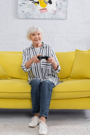 KYIV, UKRAINE - JANUARY 11, 2021: Smiling pensioner playing video game at home
