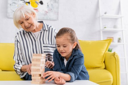 Smiling girl playing blocks wood game near blurred granny