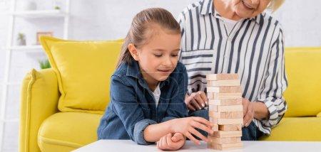 Smiling kid playing blocks wood game near granny, banner