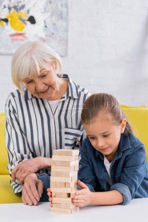 Senior woman looking at granddaughter playing blocks wood game at home