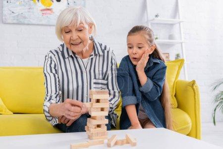 Chica emocionada mirando a la abuela sonriente jugando bloques de madera juego