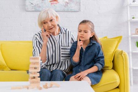 Pensive kid looking at blurred blocks wood tower game near grandmother
